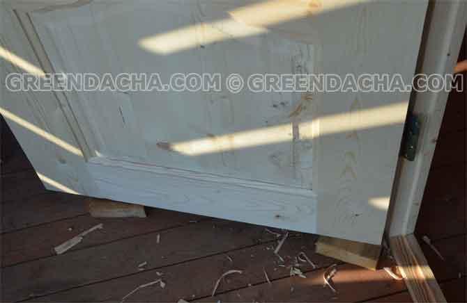 Положил деревяшки под дверное полотно и закрепил дверь в коробке.
